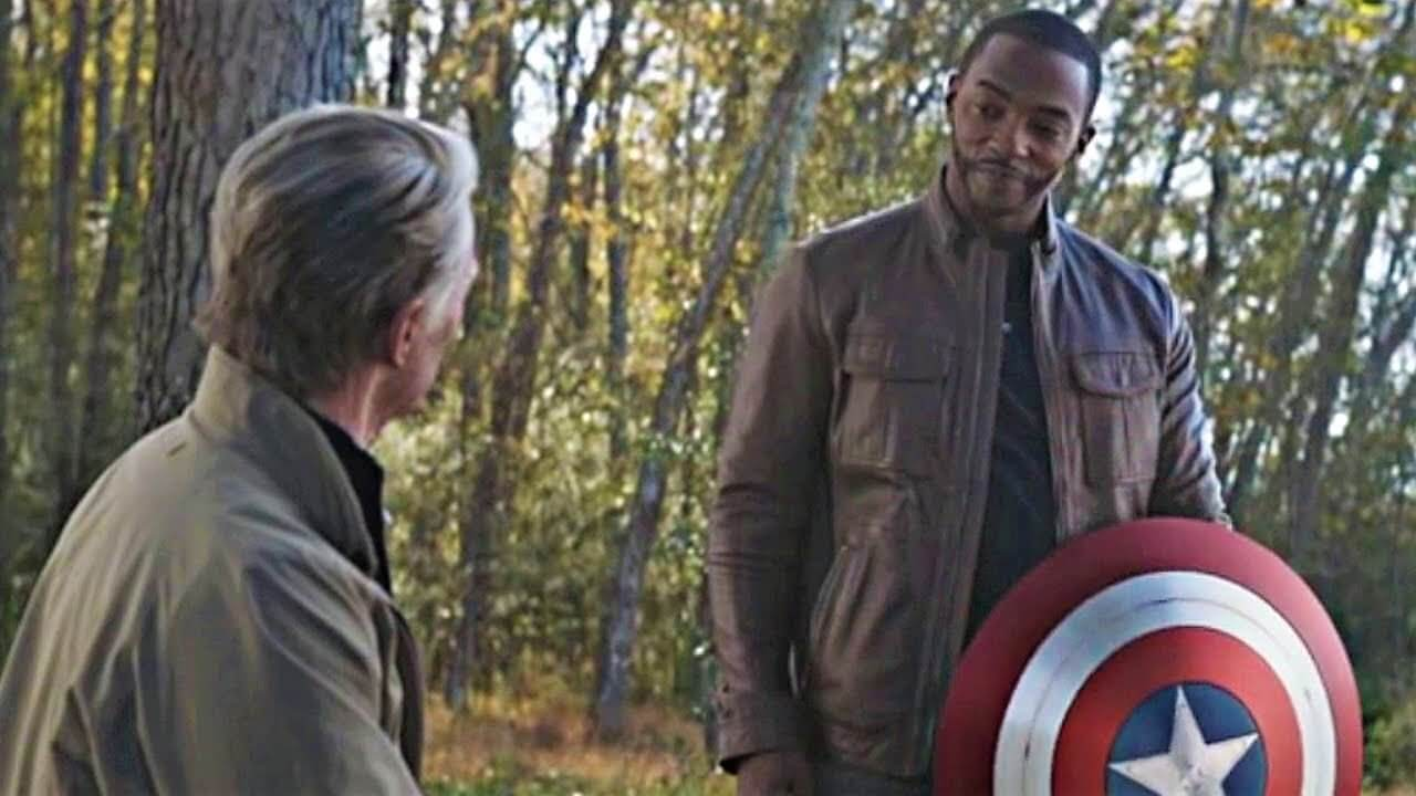 An aged Captain America hands over his shield to the Falcon