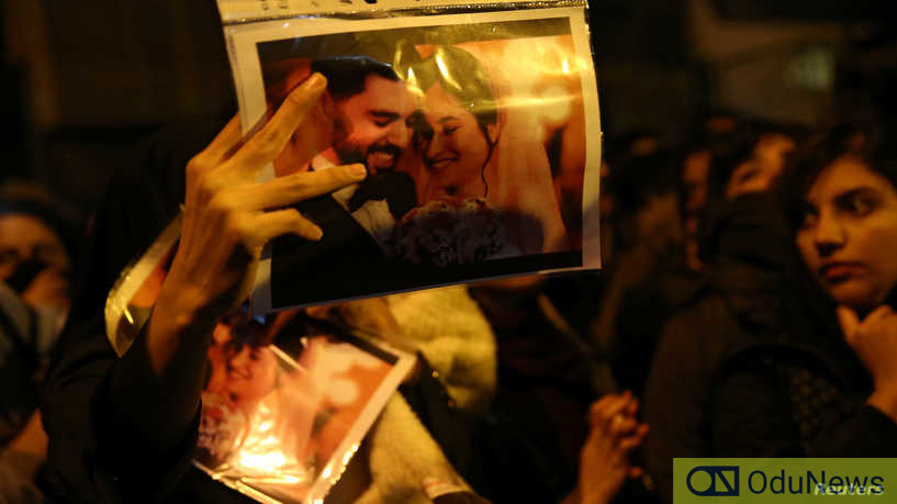A woman holds a picture of newlyweds,