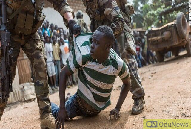 A boy is being made an example of by soldiers