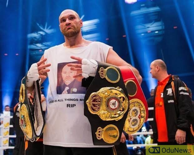 Tyson Fury shows off his Championship belts