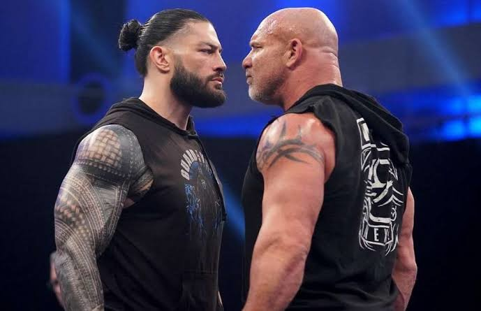 Reigns and Goldberg having a stare down in the ring