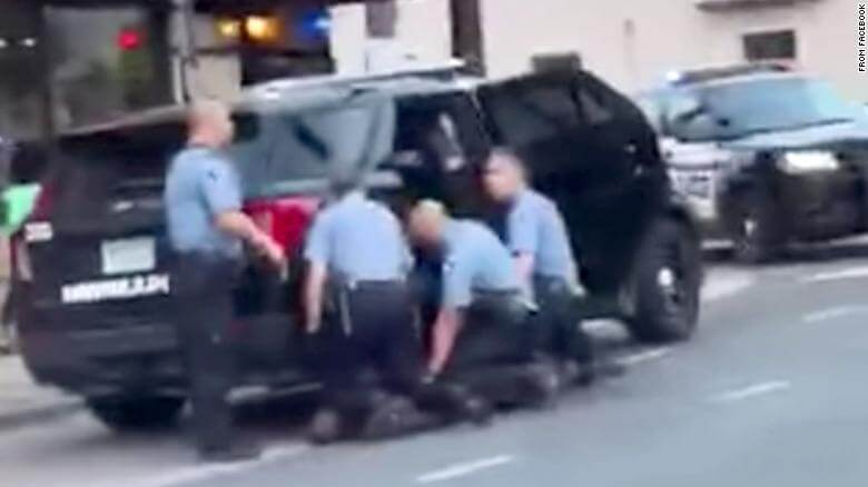 A blurry picture of the cops as they hold down George Floyd