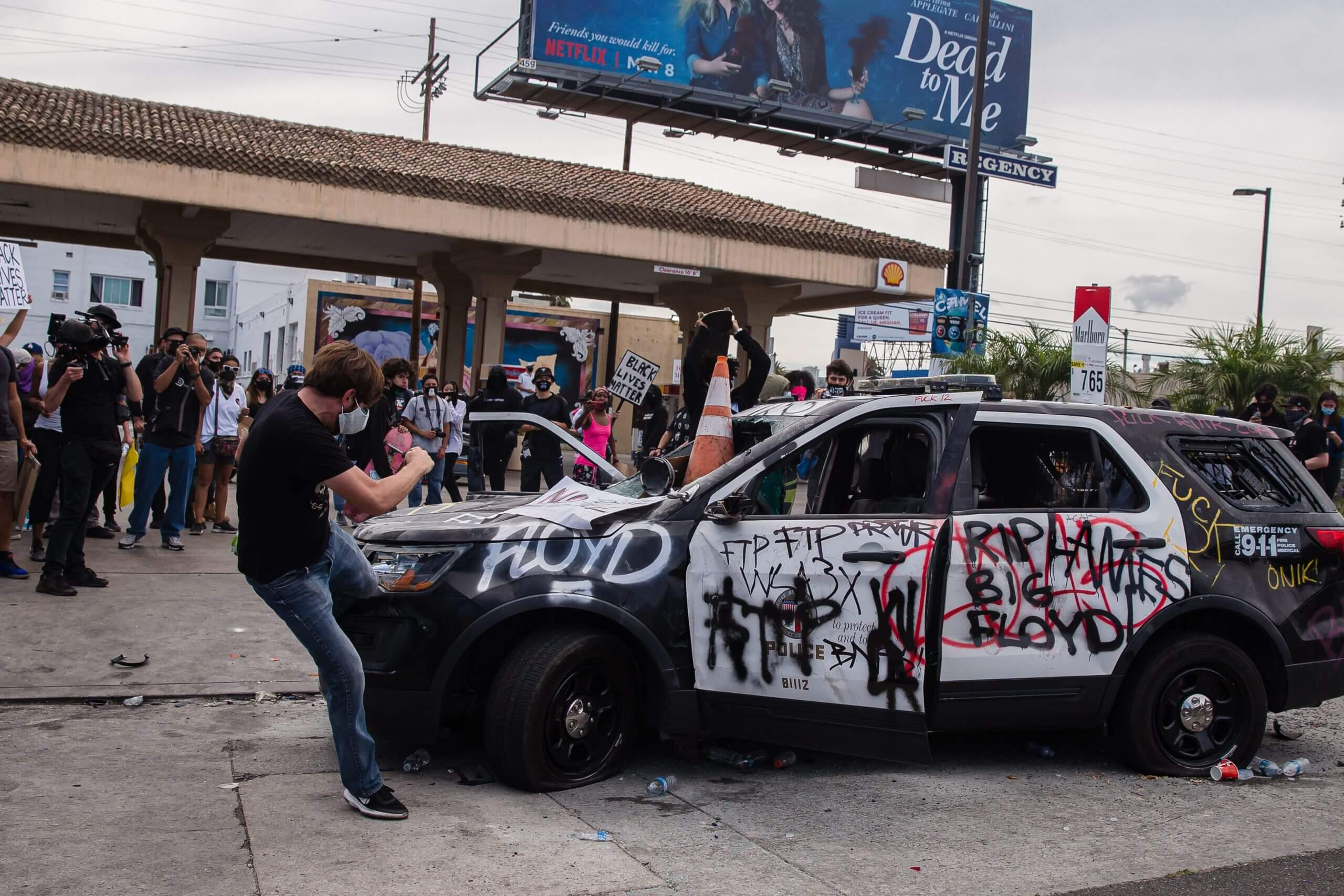 Protesters deface a police vehicle